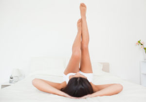 Woman laying on bed with legs sticking straight up