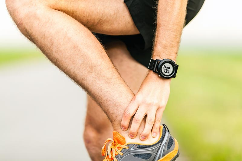 Man massaging sore calf and Achilles tendon during workout