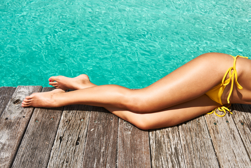 Woman legs shown while laying on a deck next to a pool