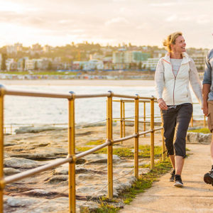 Happy and healthy middle aged active and fit couple walking outdoors by the seaside
