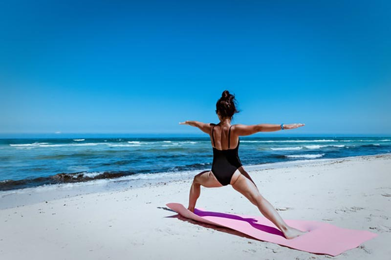 Woman doing yoga pose on the beach
