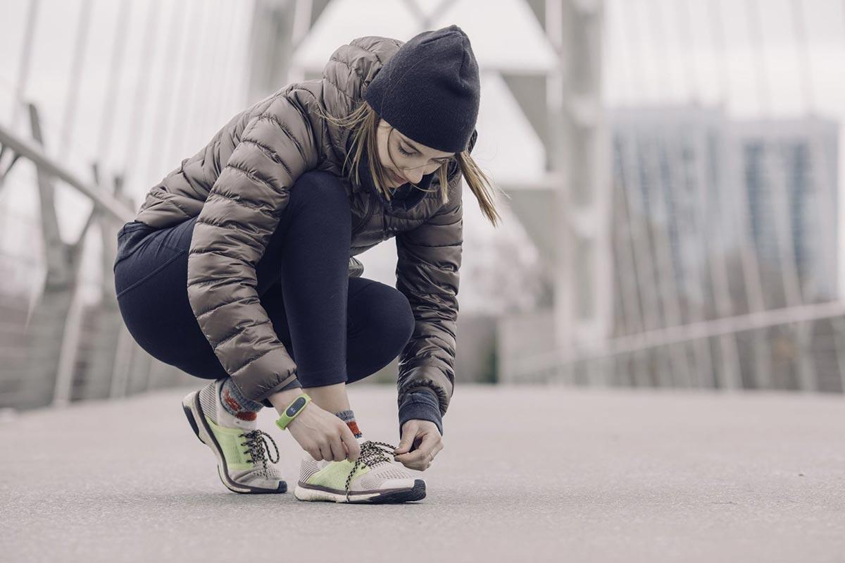 Woman in winter gear tying a shoe on a city bridge