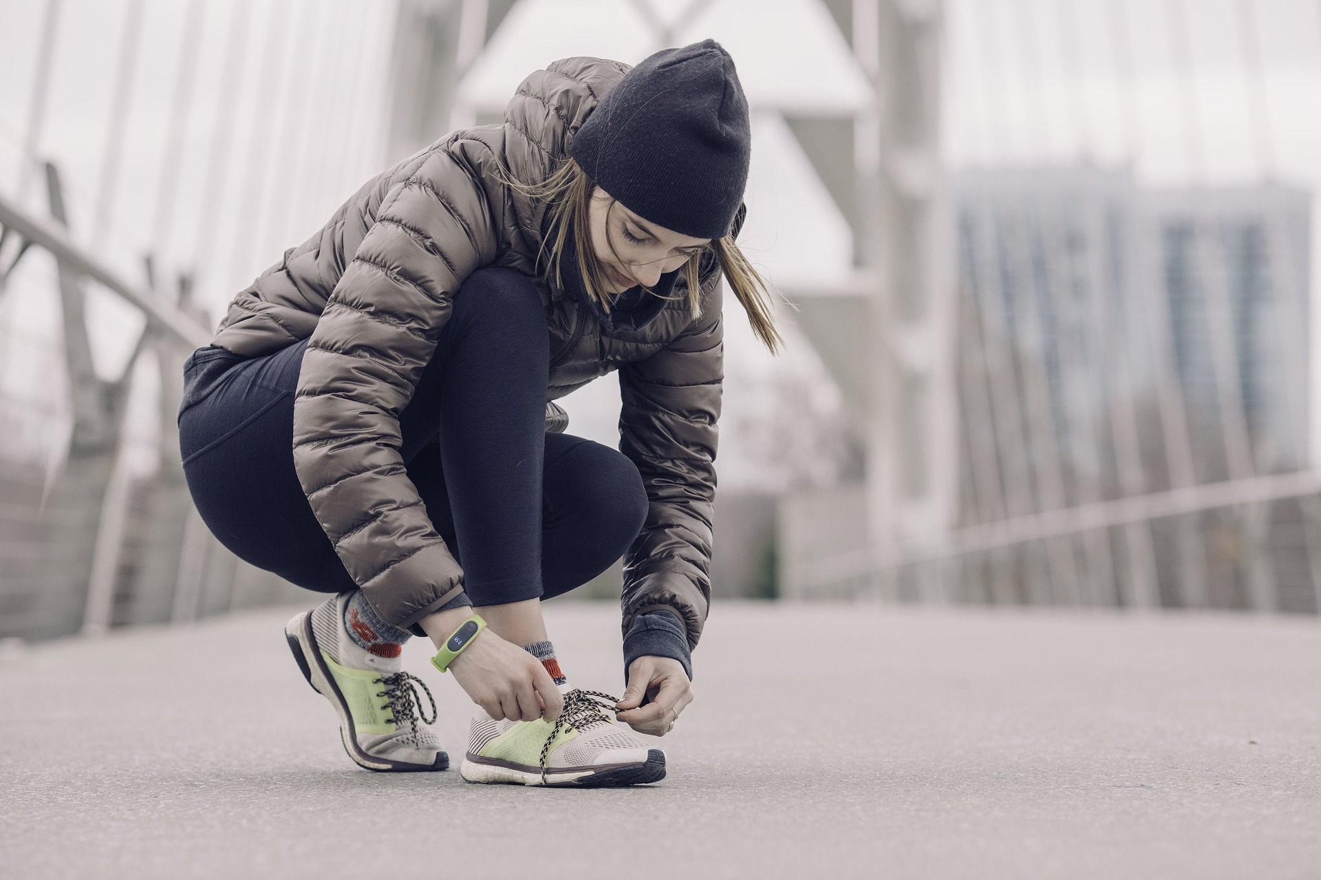 Woman in winter gear tying a shoe on a city bridge