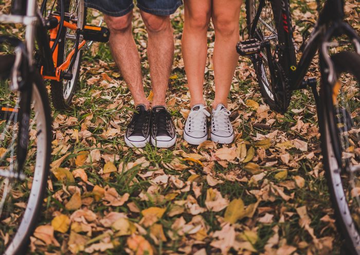 Two pairs of legs standing next to bikes on a fall day.