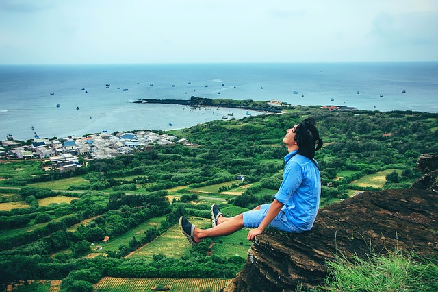 Person sitting on a cliff, living an active lifestyle