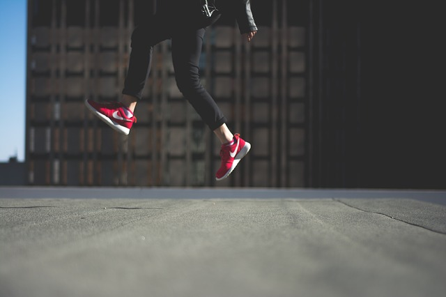 Person with red Nike shoes jumping in the air while walking