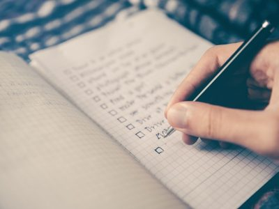 Person making a checklist in a notebook