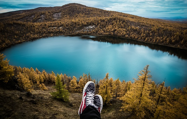 Downward view of a lake and crossed feet