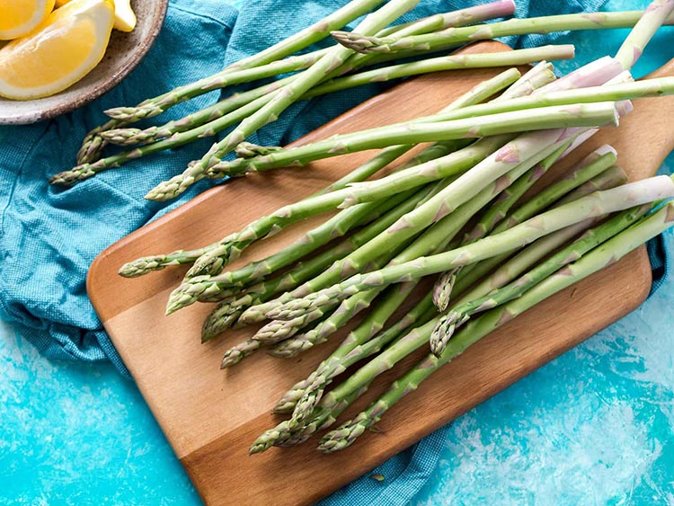 asparagus on cutting board with lemon wedges