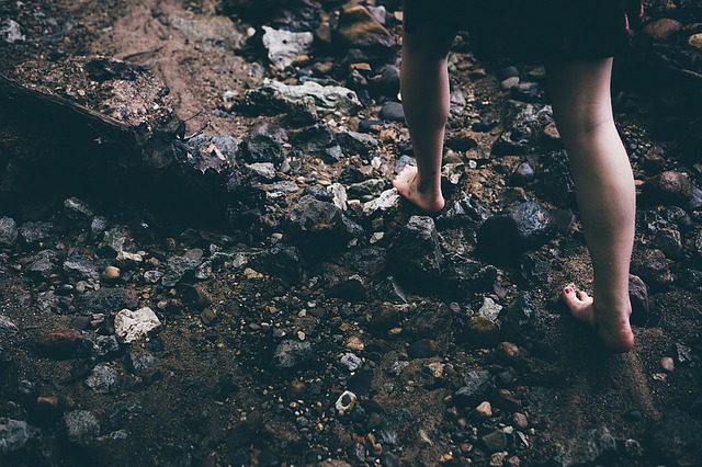 Person walking barefoot over small rocks near a river.