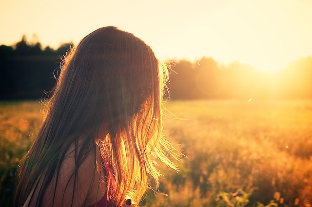 Young person walking in a field while the sun sets in the background
