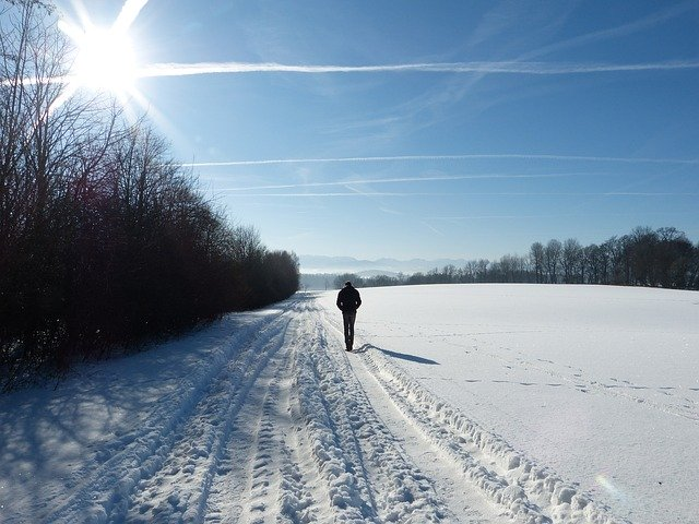 man walking in the snow with the sun shining