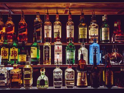 A variety of different hard liquors on a bar shelf