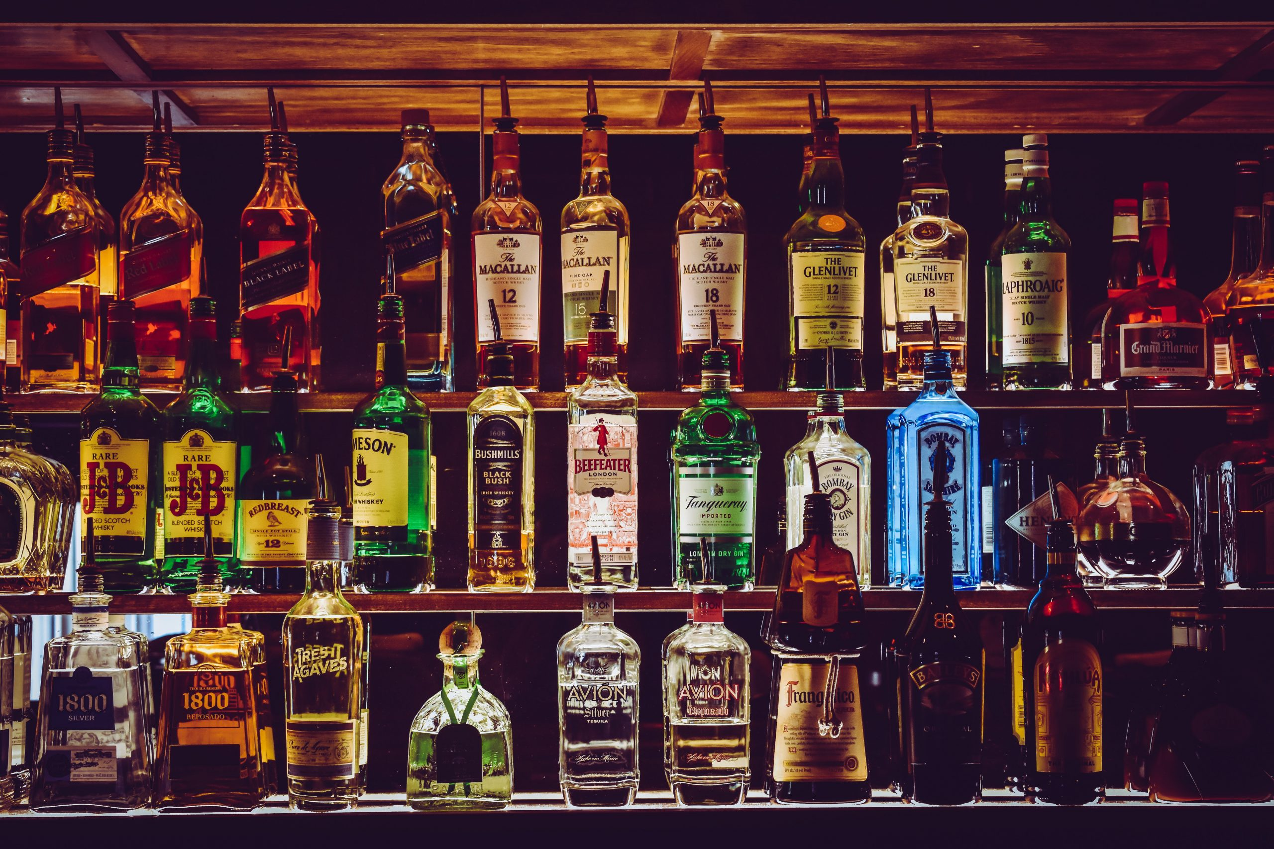 A variety of different hard liquors on a bar shelf