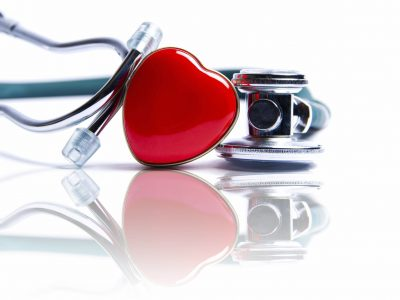 Stethoscope with a red heart in front of it.