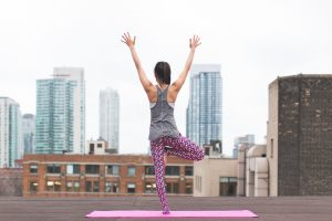 woman practicing yoga in city