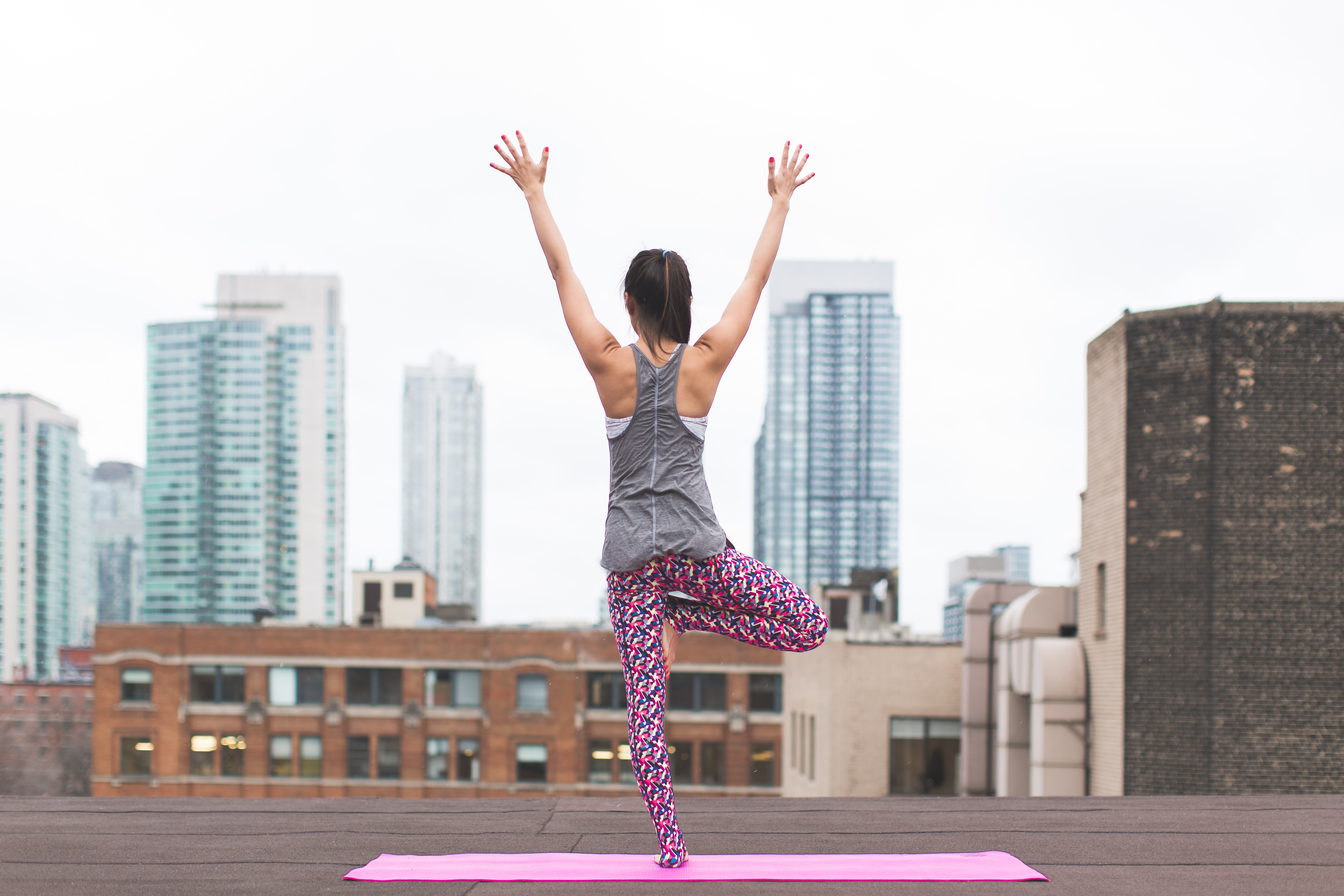 Back view of a woman standing on one leg on a yoga mat in a city