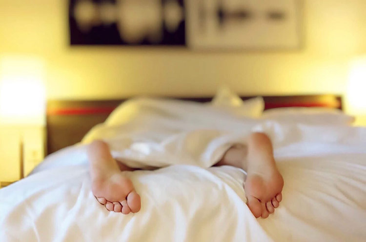 Female laying in bed with feet facing up