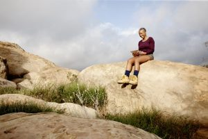 Woman using digital tablet on rock
