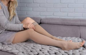woman wearing compression stockings to help varicose veins