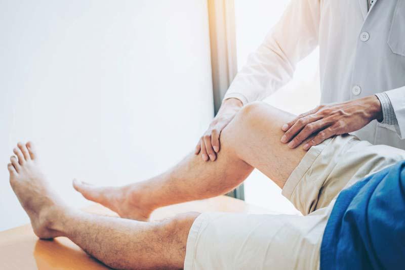 doctor diagnosing patients legs