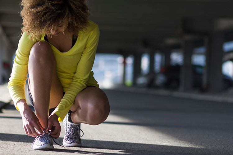 Woman tying a shoelace before workout