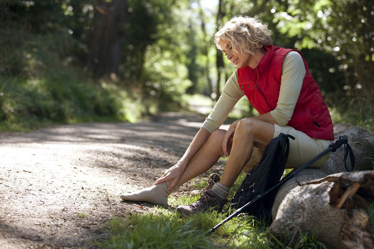 A mature woman resting beside a country path, massaging her sore feet