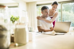 Couple using laptop in morning kitchen