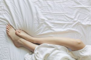 woman laying in comfortable bed with white sheets