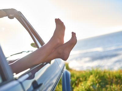 Young woman's legs sticking out the window during road trip