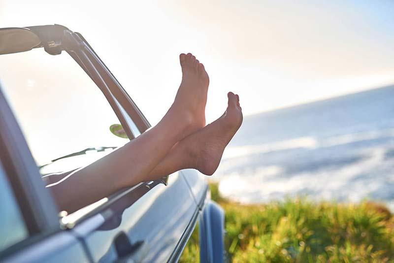 woman hanging legs outside car