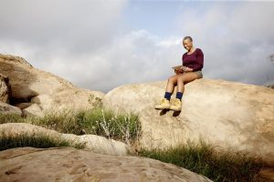 woman sitting on a rock during a hike reading from a tablet