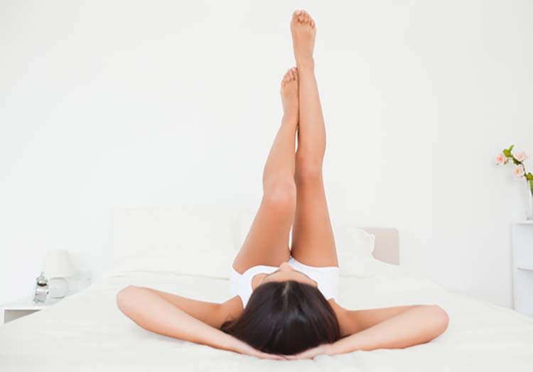 women rest legs against the wall