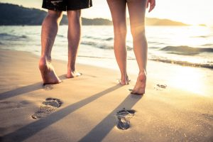 couple walking barefoot in the sand by the water