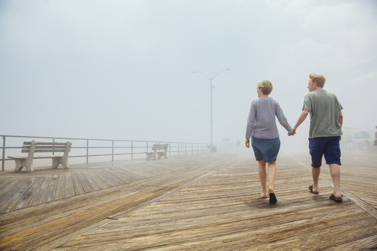 couple holding hands taking a walk on a pier