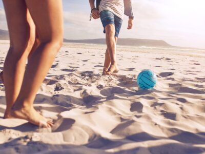 man and woman kicking a volleyball on the beach