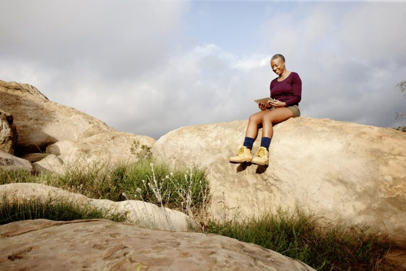 woman sitting outside on a rock reading from a tablet