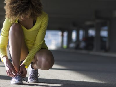 woman tying her tennis shoes before a run