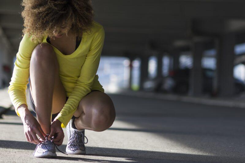 woman tying her tennis shoes before a run