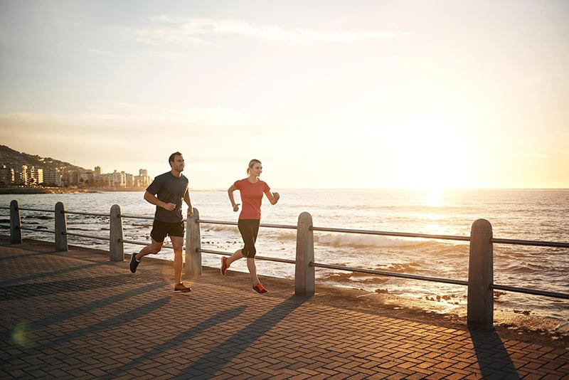 fit couple running on a pier