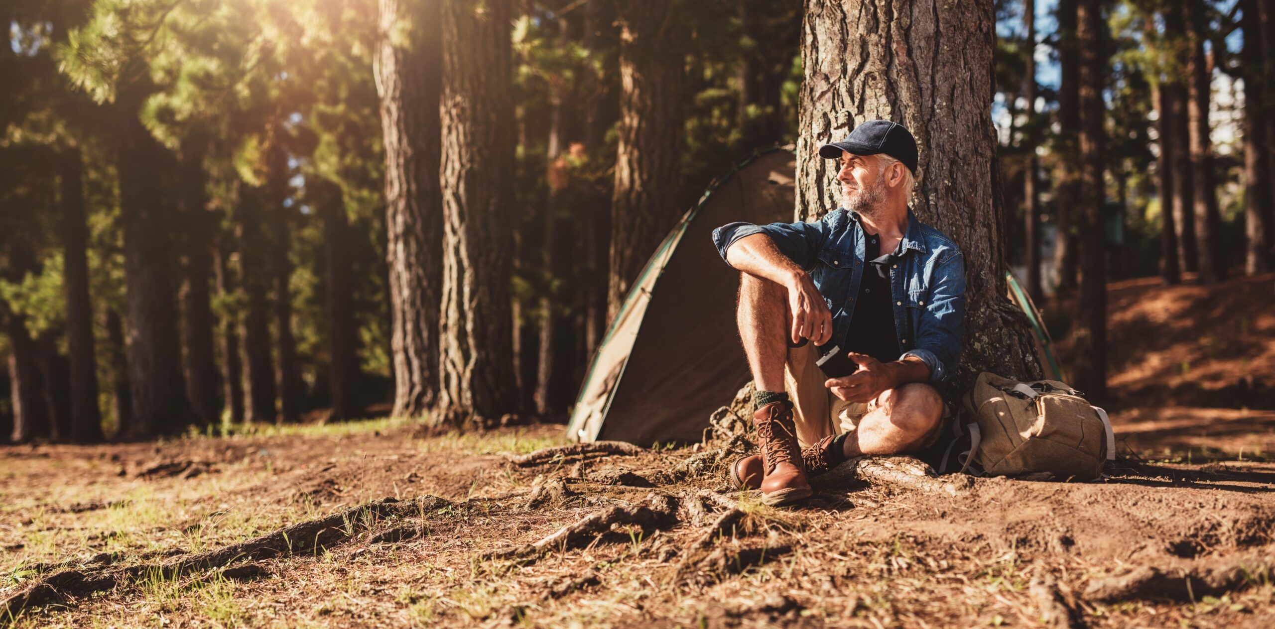 man sitting next to a tree while camping