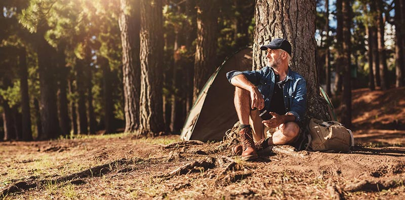 man sitting next to a tree camping