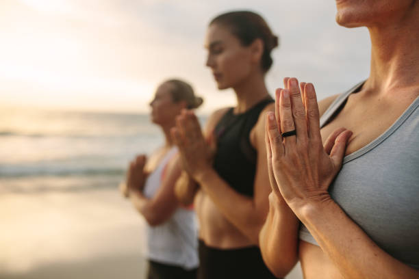 women practicing yoga on the beach