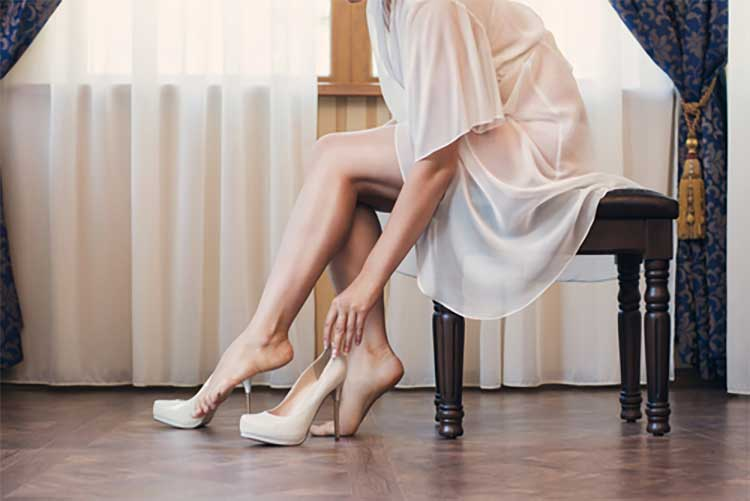female with attractive legs putting on high heels
