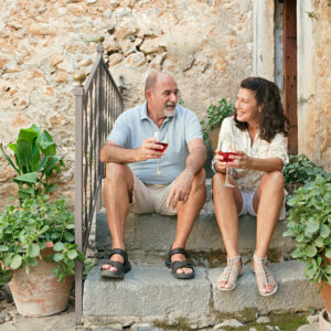 couple sitting on the steps of a luxury villa drinking wine